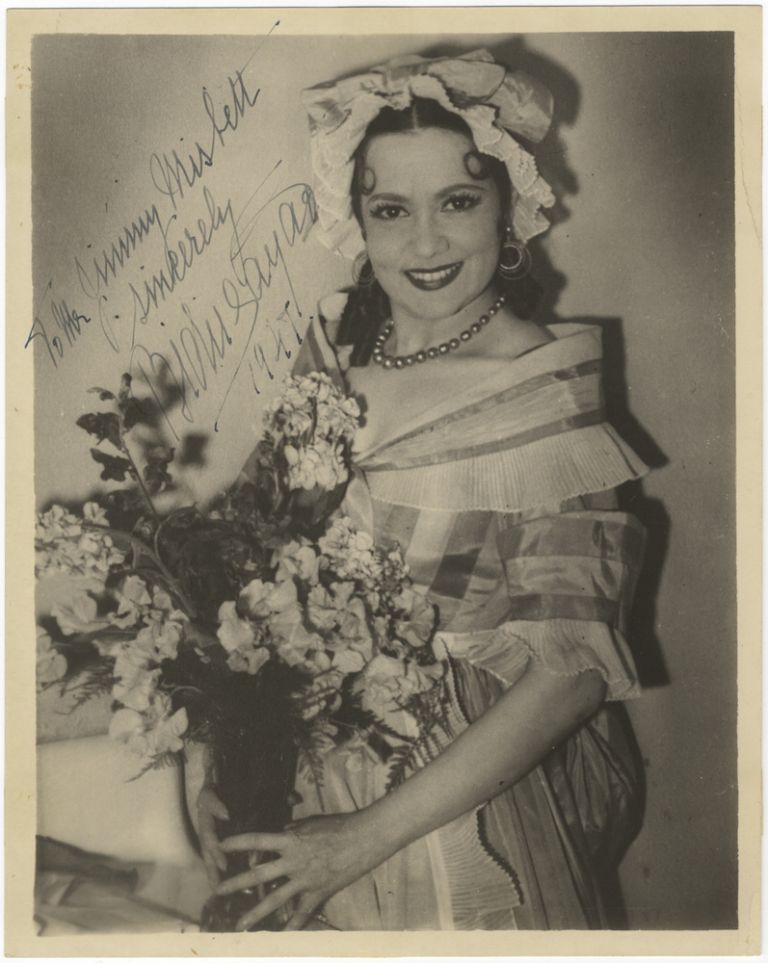 Three-quarter length role portrait photograph as Susanna in Mozart's Le nozze di Figaro, signed in full and dated 1947. Bidú SAYÃO.
