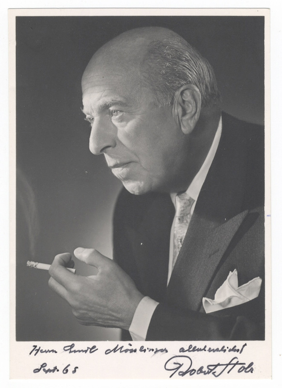 """Bust-length photograph of the noted Austrian composer and conductor in formal attire, cigarette in hand, signed, inscribed """"Herrn Emil Mösslinger allerherzlichst,"""" and dated September [19]65. Robert STOLZ."""