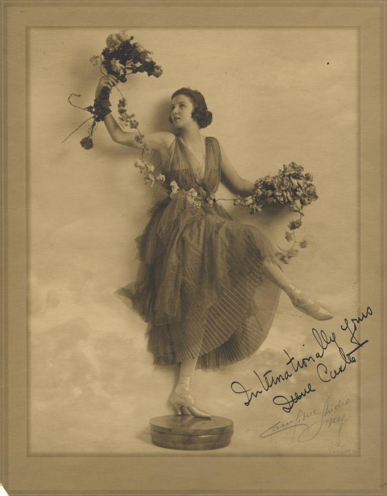 "Fine full-length original photograph of the noted ballroom dancer in costume, posed on a pedestal holding flowers in each hand linked by a single floral strand. Signed in ink at lower right: ""Internationally yours Irene Castle,"" with ""Campbell Studio NY."" in pencil below. Irene CASTLE."