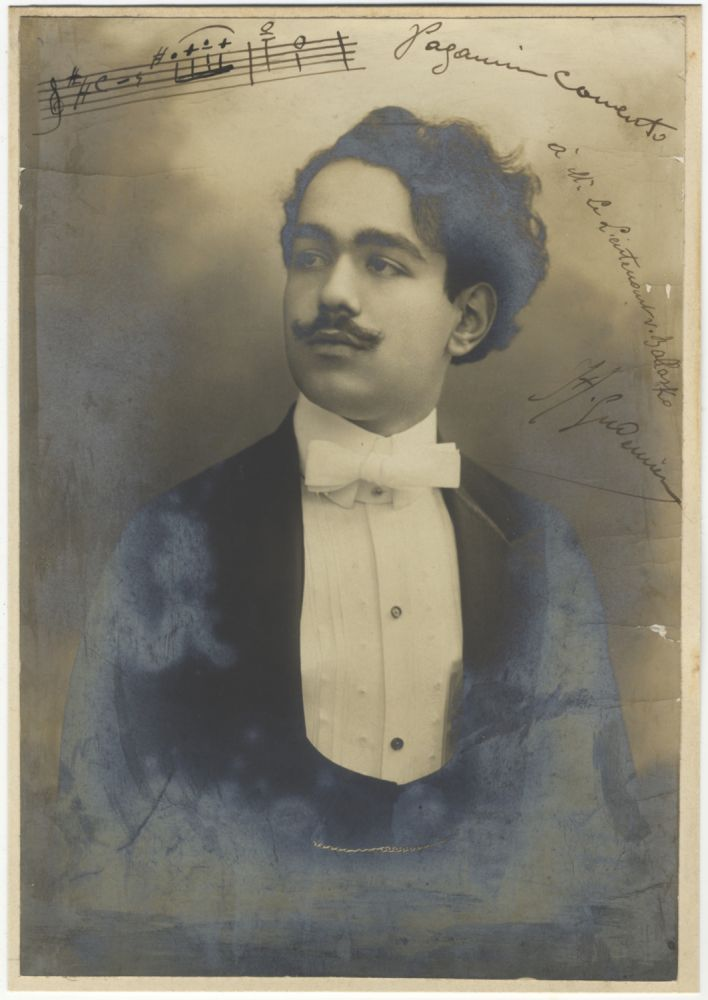 """Fine half-length photograph of this Armenian-born violinist and composer in formal dress. Signed """"H. Gudenian,"""" with a 2-measure autograph musical quotation identified as """"Paganini Concerto"""" to upper portion. Inscribed """"à Mr. Le Lieutenant v. Ballasko"""" [Lieutenant Carl Edler von Ballasko], in all likelihood a relation of the noted WWII fighter pilot Otto Edler von Ballasko (1919-2005). Haig 1885 or GUDENIAN."""
