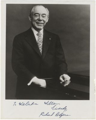 Three-quarter length photograph of the composer smiling, standing beside a piano. Signed and inscribed to Melinda Miller. Richards RODGERS.