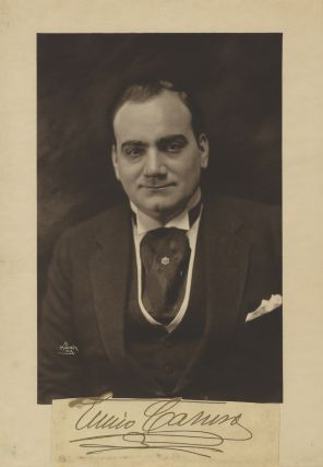 Vintage reproduction of an original waist-length Mishkin photograph of Caruso in formal dress, with his bold signature with flourish on a slip of paper mounted below. Enrico CARUSO.