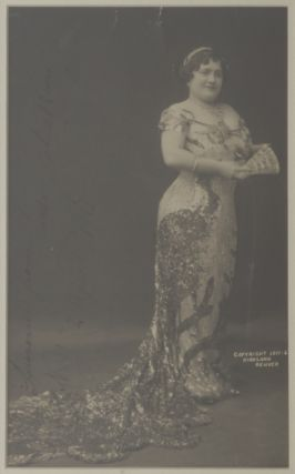 Large full-length photograph of the noted coloratura soprano in long dress with train, holding a...
